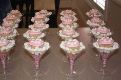 My girlfriends and I hosted a baby shower today for one of my dear friends, and we displayed the cupcakes in martini glasses with pink M and M's and Marshmellows...It was super cute, and a a guest fav!!!! Try it out!