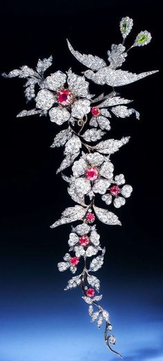 An important 19th century ruby and diamond branch brooch, designed as an articulated foliate spray surmounted by a bird of paradise, set with circular-cut and cushion shaped rubies, circular and rose cut diamons, pear-shaped peridots, mounted in silver and gold. Detaches into four brooches. English, circa 1880. #GoldBrooches