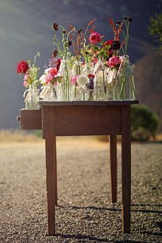 have vintage glass bottles adorned with wildflowers everywhere <3 #TheLANEWeddings and #DelphineManivet