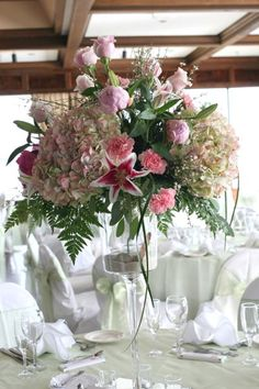 Tall centerpiece with hydrangea, stargazers and roses with shells in the vase.