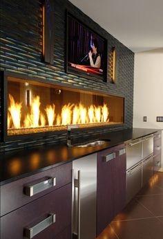 See-through fireplace in the kitchen with iridescent tile back splash and television for watching TV while cooking.  Brilliant!