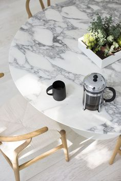 Cover the old oak table with a marble look tablecloth to hide the ink stain. Add modern wishbone chairs, limewashed flooring.