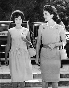 "Jackie Onassis wearing a sleeveless dress, hem down to the middle of the knee.  This outfit eventually became known as the ""Jackie"" look."