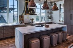 Gourmet kitchen features three industrial copper pendant lights illuminate a gray wash center island fitted with a white marble waterfall countertop fitted with a stainless steel dual sink and a gooseneck faucet lined with gray nailhead ottomans doubling as bar stools.