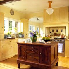 love the yellow cabinets especially paired with the natural wood island