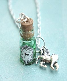 "This necklace features a unicorn's blood potion pendant. The glass vial/bottle pendant measures 2 cm tall and is securely attached to a silver tone chain necklace that measures 24"" in length. A Tibeta"