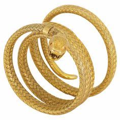 Antique Gold Mesh Coiled Serpent Bracelet; a woven gold coiled mesh bracelet terminating in an open-mouthed serpent, accented by 2 small round ruby eyes, circa 1840.