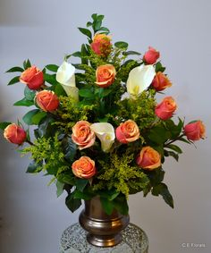 Coral roses and white calla lily arrangement