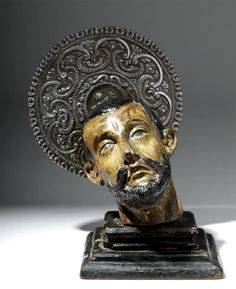 Latin America, Mexico, ca. 18th century CE. A hand-carved/painted wood severed head of Saint John the Baptist tilted and bleeding after his execution. The visage comprised of inlaid glass staring eyes, parted downturned mouth, sallow skin, and realistic bone structure is uncannily naturalistic and displays the high key emotional and dramatic influences of Spanish Art. Silver halo.