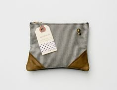 Image of a small charcoal + cream striped zipper pouch with leather corners and a METAL zipper