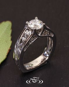 Custom Platinum organic trellis style mounting showcasing a beautiful 1ct round brilliant cut diamond. Pierced curling vine and engraved leaf details flow down the shoulders with accent diamonds.