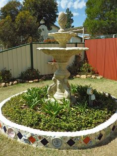 I created some whimsical charm to my garden with a water fountain and round mosiac garden bed.