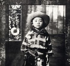 """Tomie Arai, 'Peach Boy', 2003, etching - The black and white etching of a Chinese boy staring blankly ahead and wearing an oversized cowboy suit, reminds Robert Lee, co-curator of """"Infinite Mirror: Images of American Identity,"""" of himself. Lee knows the complexities of assimilation: his parents emigrated to the U.S. from China, he's named after Robert E. Lee, the Confederate Civil War general, and as a child, his folks dressed him like a cowboy, too."""
