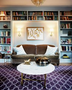 Traditional Living Room: Built-in bookcases surrounding a brown couch and a pair of wall sconces.