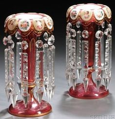 lighting, Czechoslovakia, A pair of Bohemian cranberry glass girandoles [or lustres], gilded foliage and trim, the over turned rim with raised medallions enamel decorated with alternating portraits and slowers, cut prism pendants. Circa 1801-1900