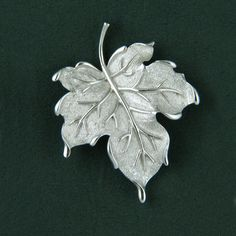 Beautiful, dimensionally curved maple leaf pin in gleaming silvertone. Stem, leaves and veins are polished while leaf surface has a granular texture. Pin measures approximately 1-3/8 x 1-7/8 inch. Sig