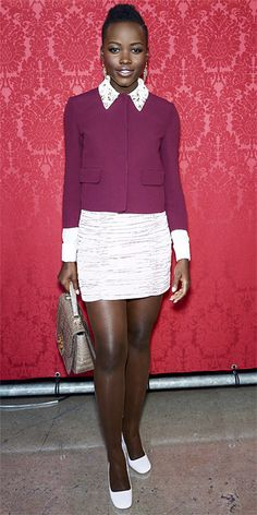 Lupita Nyong'o wearing head-to-toe Miu Miu: burgundy silk cady jacket with an embroidered collar, white cloquet-silk shirt and blush pink silk-faille skirt, styled with a taupe croc handbag and lilac patent heels.