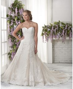 604 - This fit and flare gown embraces the lace design all around the bodice and skirt of the dress.