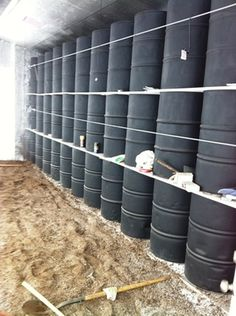 "The thermal ""battery"" in a passive solar greenhouse - barrels of plain old water on the north wall of the structure. Warmed by day, they release their heat at night."