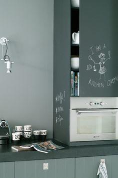De grijs geschilderd achterwand met matte krijtverf van Pure & Original, in een tintje lichter dan het antracietgrijs van de kastjes.