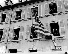 Tout le monde est à ses fenêtres dans ce bâtiment qui arbore le Stars & Stripes pour fêter les libérateurs, le 14 juillet 1944.