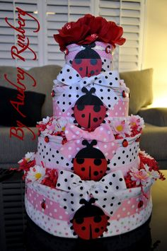 * {Inspirational} Lady Bug Diaper Cake. Easy DIY baby shower gift ~ diapers wrapped in bunny rugs, tied with ribbon and finish off with flowers and ladybugs. Just beautiful!