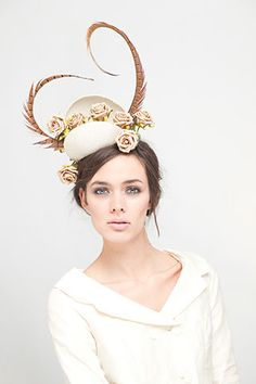 Clam flower fascinator with feathers.