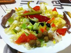 Amanida d'escarola amb tomàquet, pebrot, calçots, olives, bitxo i anxoves