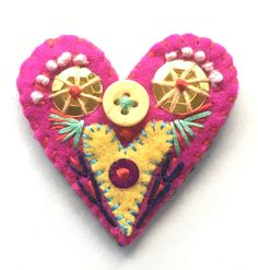 A pretty, handmade heart brooch. Embellished with many colors of string, a button and shiny sequins. A perfect addition for Valentines Day!  A safety pin is carefully sewn to the back of the heart.  size: about 4.44 cm x 4.44cm x .31cm