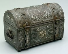 Iron and silver strongbox, rectangular with dome top and strap hinges, top and sides with applied classical silver medallions with trophies of agriculture, figures and soldiers, elaborate engraved birds, vines and arabesque-style decoration throughout, double locks activated by pulling feet, probably Middle Eastern, possibly 19th century or earlier, 7-1/4 x 12 x 6 inches. (Treasure Chest)