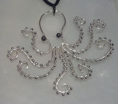 Hey look, heres a silver-plated wire octopus necklace with silver bead suction cups and hematite eyes! He obviously needs to live on your neck.: