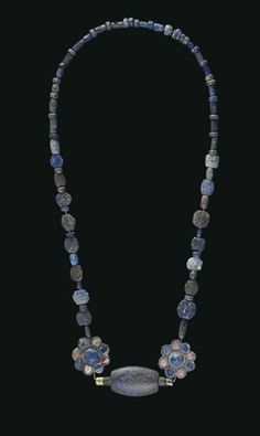 A BACTRIAN LAPIS LAZULI, CARNELIAN AND CHLORITE BEAD NECKLACE  CIRCA LATE 3RD MILLENNIUM B.C.  Strung with lapis lazuli beads of various forms interspersed with lapis lazuli spacers, graduated in size, centered by two chlorite compartmental rosette beads, inlaid with lapis lazuli and carnelian, a large lapis lazuli ovoid bead in between with a gold overlaid copper projection on each end