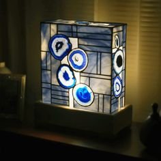 Our blue colored agate lamp 1960 is one of the larger lamps in the collection. It contains blue colored agates suspended in a pattern of blue stained glass