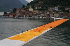 THE FLOATING PIERS BY CHRISTO - Lake Iseo, Italy, 2014-16 - From the evening of June 15 to the evening of June 17, teams unfurl 100,000 square meters of shimmering dahlia-yellow fabric on the piers and pedestrian streets in Sulzano and Peschiera Maraglio