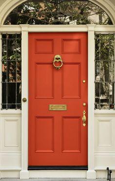 Puerta rojo coral con cristalera alrededor.
