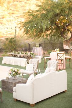 Private estate wedding in blush pinks, and pastel lavenders and light blues. Florals of blush peonies and lavender roses. Backyard reception with long floral garlands and decorated sweetheart swings for the bride and groom. Vintage cream colored furniture brought in for seating.