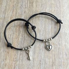 Black Leather matching bracelets with silver charms  These lovely bracelets are made with genuine leather cord. Designed for couples  Both bracelets are adjustable  Includes Gift Box  Please feel free to contact me if you have any questions  These bracelet will be shipped by USPS First Class as soon as the payment is been received  For more Couples Bracelets: https://www.etsy.com/shop/Fanfarria?section_id=17115613&ref=shopsection_leftnav_10  Check all Fanfarrias products…
