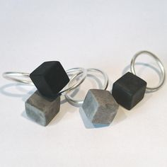 Concrete Cube Ring in a minimalist Nordic design, made from stone cast and silver to give it a soft a smooth feel and the aestetics of industrial concrete and cement. Note that surface and appearance might vary from the image as all of our jewellery are handmade.  Choose between sizes 49-55 ----- About the designer: In our first line of jewellery, we seek to break with the usual notion of how jewellery should look like. We have chosen a material that is raw and industrial as a starting…