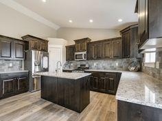 Dark Kitchen Cabinets and Light Countertops. Steve Austin Homes. Brown Cupboards, Kitchen Flooring, Home, Stained Kitchen Cabinets, Staining Cabinets, Kitchen Remodel, Kitchen Style, Dark Wood Kitchen Cabinets, Kitchen Design