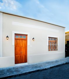 Super cute facade of an old house with a gorgeous wooden door. By Taller Estilo Arquitectura
