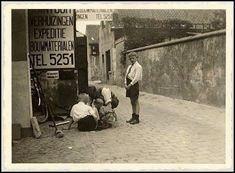 1930-1935 – Breda. Portret van Jan Verlegh van verhuisbedrijf Verlegh aan de Wilhelminastraat 13 (later genoemd Ginnekenweg) staand in de steeg bij de poort. Linksonder op de rug gezien in witte blouse vermoedelijk Henk Verlegh.