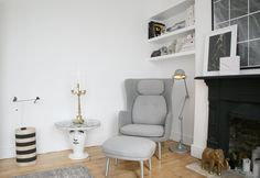 A Ro chair and stool from Fritz Hansen, Fornasetti Side table and vintage Jielde floor lamp featured in this living room nook.