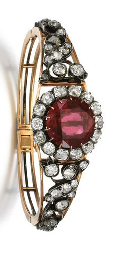 Garnet and diamond bracelet, late 19th century The detachable central plaque set with a circular-cut garnet, within a border of cushion-shaped diamonds, to a similarly set bracelet, decorated with floral motifs, inner circumference approximately 170mm, accompanied by case stamped Sandoz.