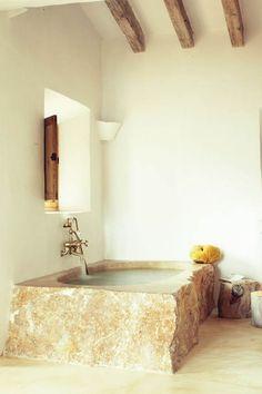 Esta banheira é perfeita para tomar um banho relaxante durante horas, sozinho ou com outros. Pedra esculpida em uma sala de paredes simples, contrasta com a linha de torneiras antigas que é tendência e calor.  Fotografia:  France AD Revista.