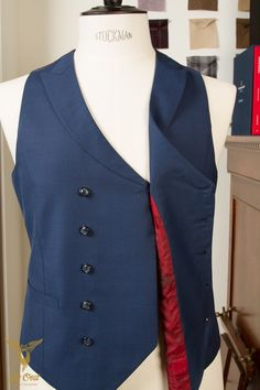 Double Breasted 5x2 Knoops Blauw Vest Met Peak Lapels, 2 Heupzakken En Een Rode Contrasterende Achterzijde Met Gesp. Double Breasted 5x2 Button Blue Waistcoat With Peak Lapels, 2 Hip Pockets And A Contrasting Red Back With Strap Buckle.