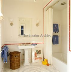 A line of red tiles frames the contours of this contemporary family bathroom-We'd use blue