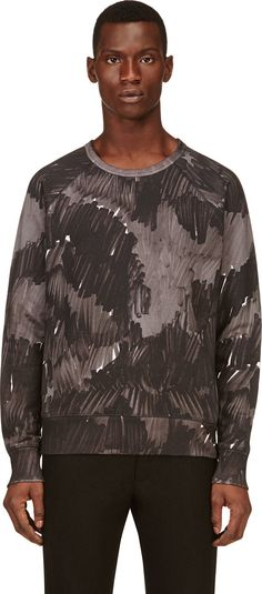 Long sleeve pullover sweatshirt in black and grey modified camouflage print. Fine stretch ribbing at crewneck collar, sleeve cuffs, and hem. Tonal stitching.