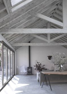 The living room at the Cow Shed, a Victorian barn conversion by Nash Baker Architects in Suffolk, showing the vaulted ceiling with exposed lime washed timber roof trusses, and the wood burning fieplace. Photo by Nick Guttridge Exposed Trusses, Roof Trusses, Open Ceiling, Floor To Ceiling Windows, White Ceiling, Cow Shed, Timber Roof, Timber Ceiling, Wood Ceilings
