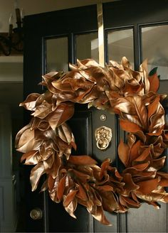 Gold magnolia wreath!  I started out by collecting a few magnolia branches.  The fresher ones were easier to work with.  I then separated each leaf and sprayed them gold.  After I let them dry, I bundled them in groups of three with floral wire and then wired all those onto a 15' metal wreath from... and voila!