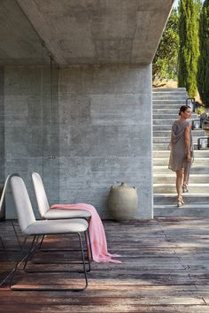 Outdoor dining chair. Elegant, with or without armrest, upholstered. Belgian design by Gerd Couckuyt for Manutti. Concrete walles. Concrete stairs.